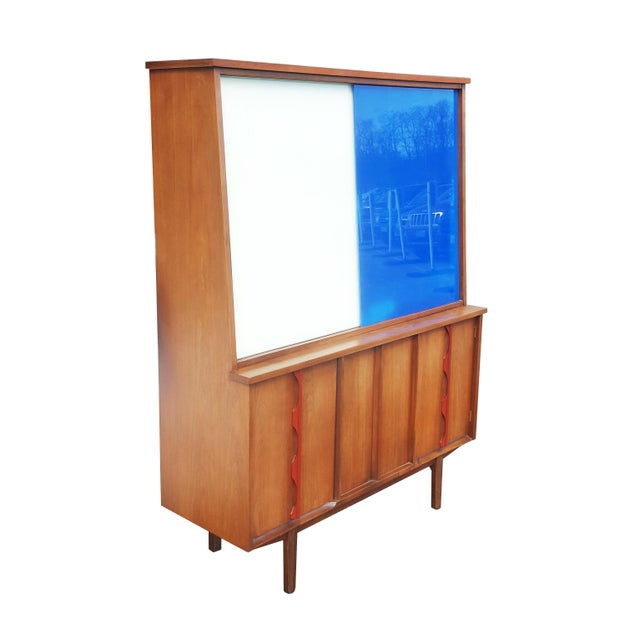 Mid-century modern display cabinet. American made. Featuring 2 shelves on the top part and 1 shelf behind each door on the...