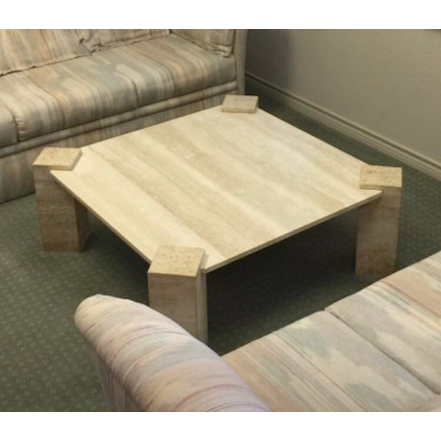 A stunning polished Travertine coffee table featuring a thick polished travertine top resting on a base of four triangle....