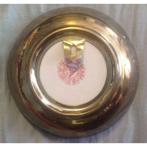This plate features beautiful lotus and bird design with a brass rim. A brass hook on the back makes it ready to hang on...