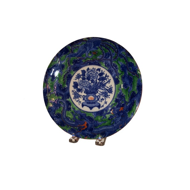 An antique Chinese plate with florals and dragons in blue, green and white with a small amount of red. Four marking on back.