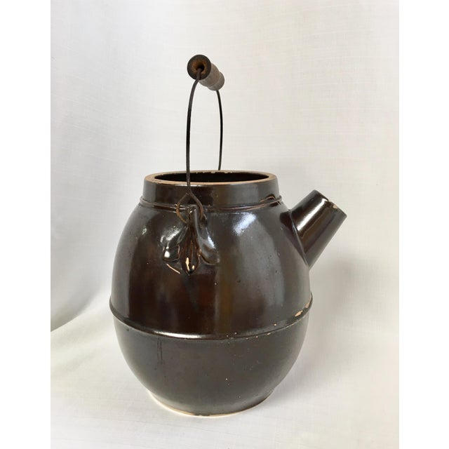 Antique Stoneware Batter Jug in a warm coffee colored glaze with original heavy gauge wire & wood handle. Piece is...