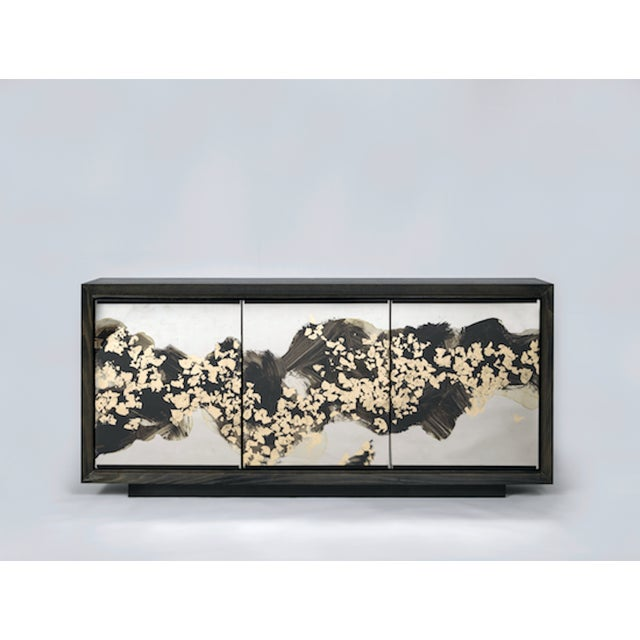 The Faubourg Cabinet by Studio Van den Akker features églomisé glass panels by artist Emma Peascod. The cabinet is...