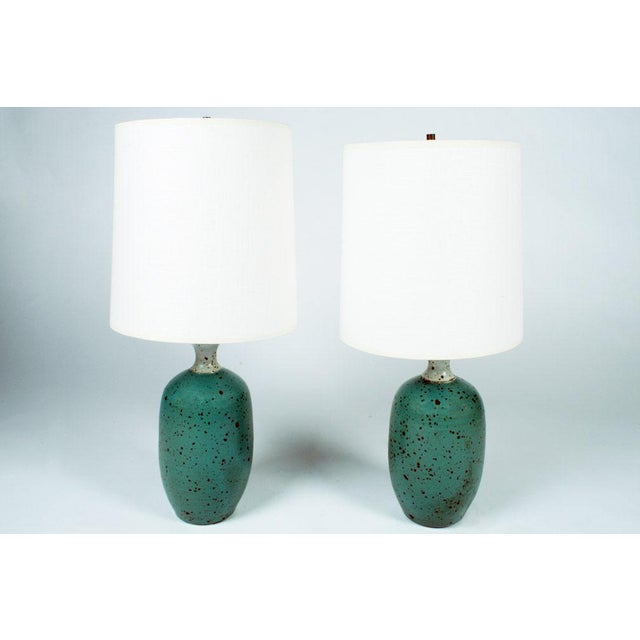 A diminutive pair of table lamps, each individually thrown into an urn-shape form with a lipped neck then finished with a...