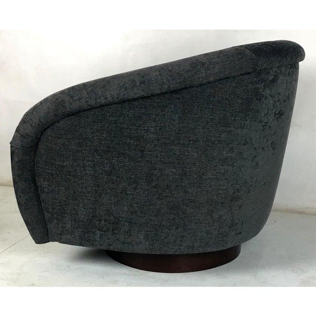 Pair of Milo Baughman roll arm swivel chairs raised on walnut veneer circular bases. The pair have been freshly...
