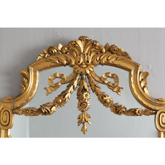 Outstanding French Louis XVI style swags & bows wall mirror finished with fine gold finish. Center floral crest flanked by...