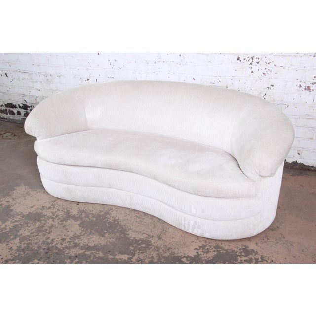 A unique kidney-shaped sofa, circa 1970s. The sofa features a nice sculptural modern design, with a curved arched back and...