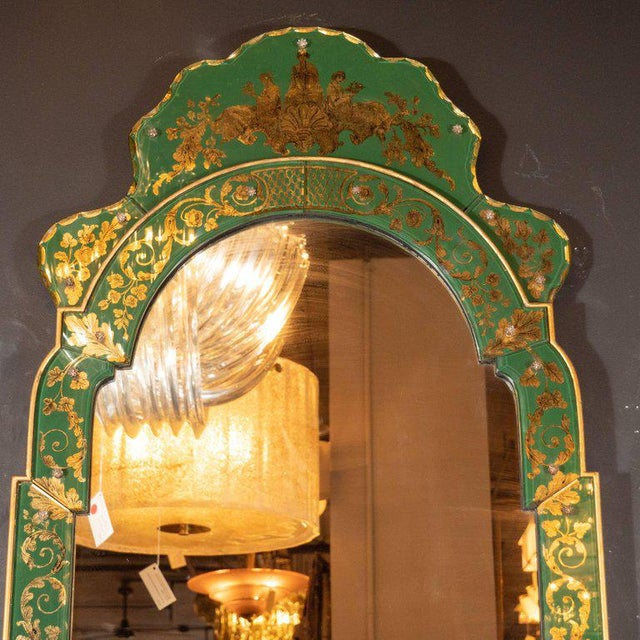 This elegant mirror was realized in the United States, circa 1950. It features an arch form body of giltwood with...
