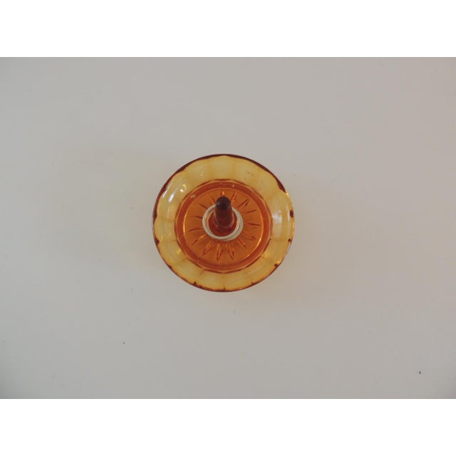 "Round amber color glass ring holder. (Rings not included) Size: 3.5"" D x 2.5"" H."