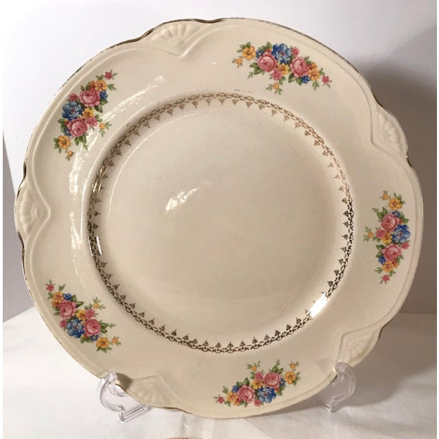 Beautiful set of four dinner plates featuring a pretty floral pattern with gold trim and a scalloped shaped edge. Marked...