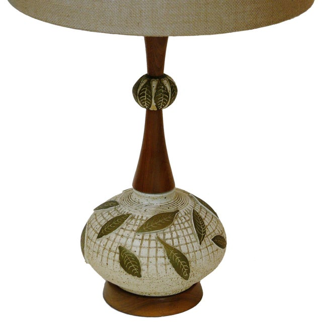 A whimsical pair of ceramic lamps with oiled walnut trim and ceramic finials. The shades are not original.