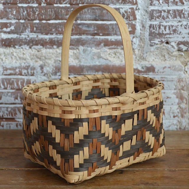 Offered is a split white oak small market basket with handles by Cherokee master basketmaker Carol Welch; featuring a...