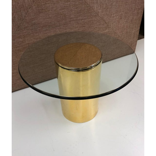 Brass side table by Pace. Cylindrical brass base with round glass top.