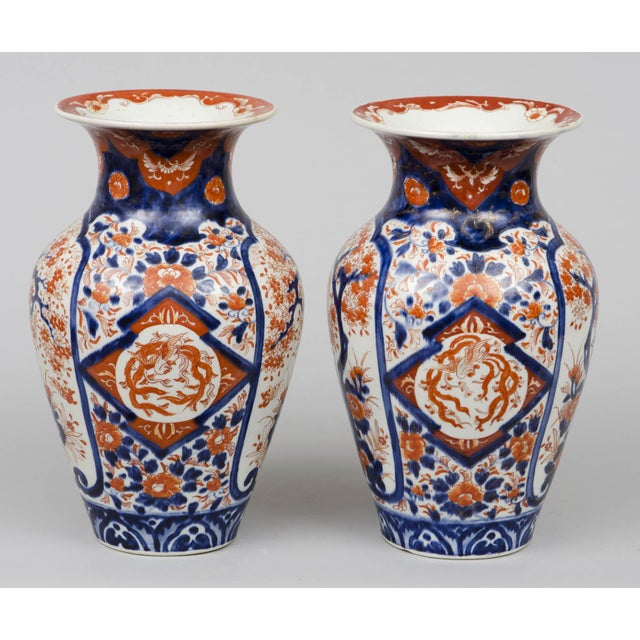 Pair of Japanese Imari porcelain vases of baluster form with short flared necks decorated with shield-shaped panels...