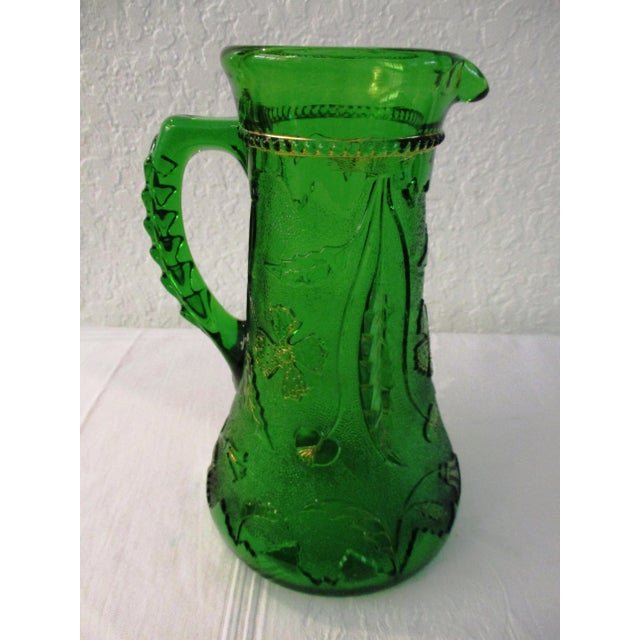 Gorgeous 1800s Northwoods emerald green glass pitcher featuring a raised ornate botanical motif around perimeter with gold...