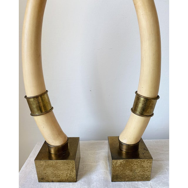 Statement bookends! Stunning pair of large faux elephant tusk with brass accents and base bookends by Chapman, 1976. Some...