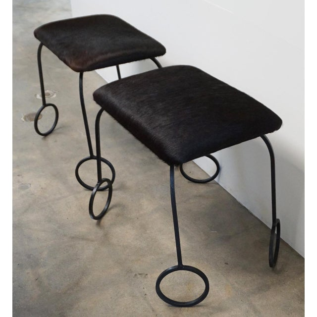 Furry cowhide and iron stools with bubble wand legs. Perfect addition around a low coffee table. New upholstery.
