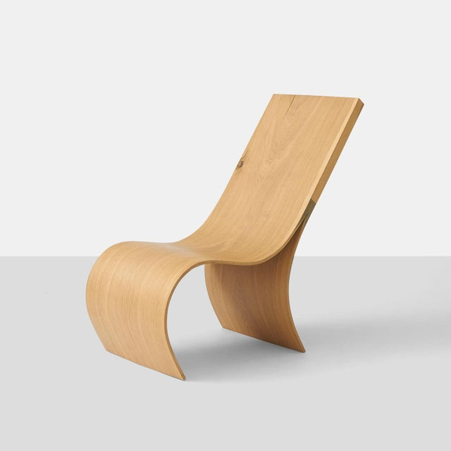 A hand formed lounge chair made from a solid piece of oak from naturally fallen trees by German craftsman Kaspar Hamacher....