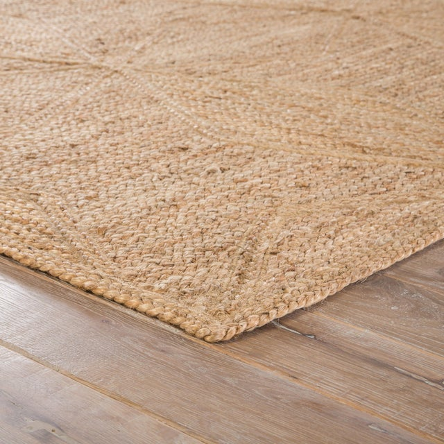 This jute area rug provides a staple to transitional homes with a neutral colorway and organic style. A geometric weave...