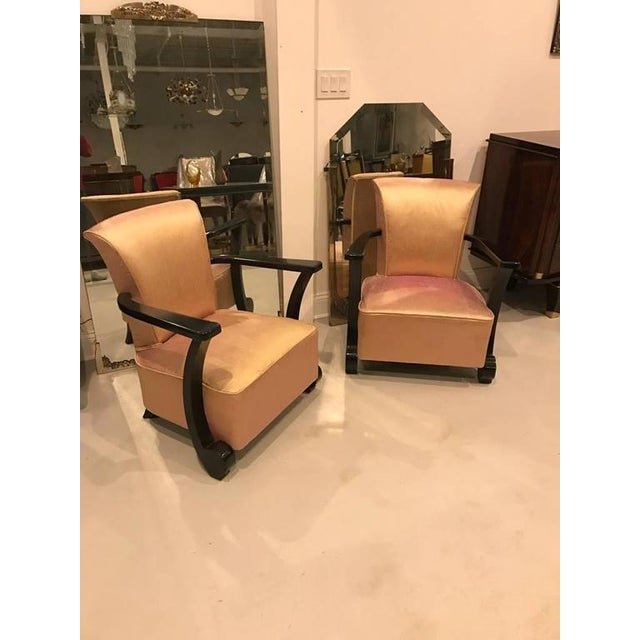 Stunning pair of French Art Deco club chairs. Having beautiful deco ebony lacquered legs and pink upholstered fabric.