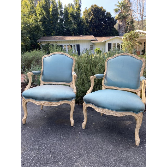 Pair of French Bergere upholstered arm chairs. Painted Beech wood. Covered in Holly Hunt teal fabric; requires re-...