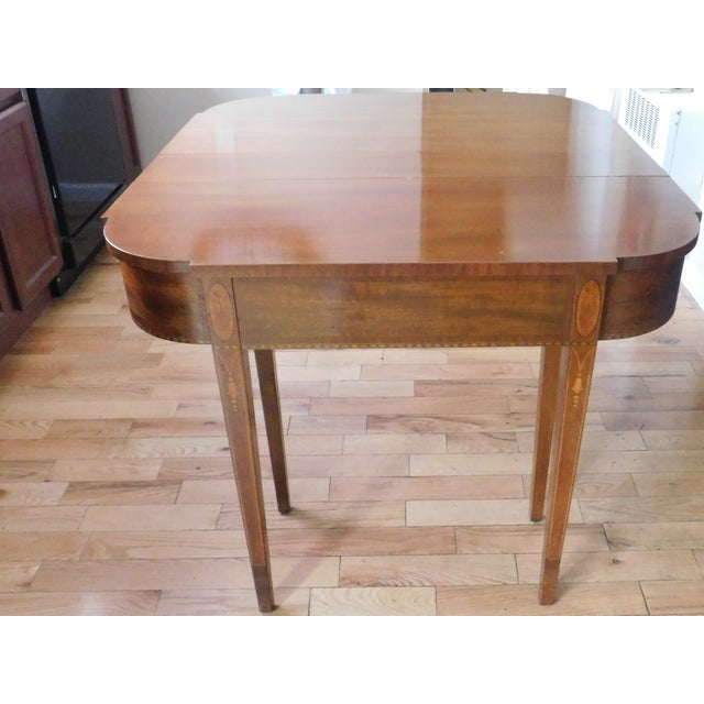 This elegant and VERY functional antique mahogany marquetry demi-lune extension entrance table/dining table/card table is...