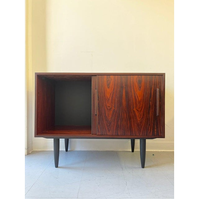 A functional Danish Rosewood Cabinet Credenza. Accessed by two sliding doors the interior is divided into two...