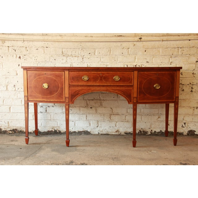 Stunning inlaid mahogany American sideboard buffet from the Historic Williamsburg line by Baker Furniture. This sideboard...