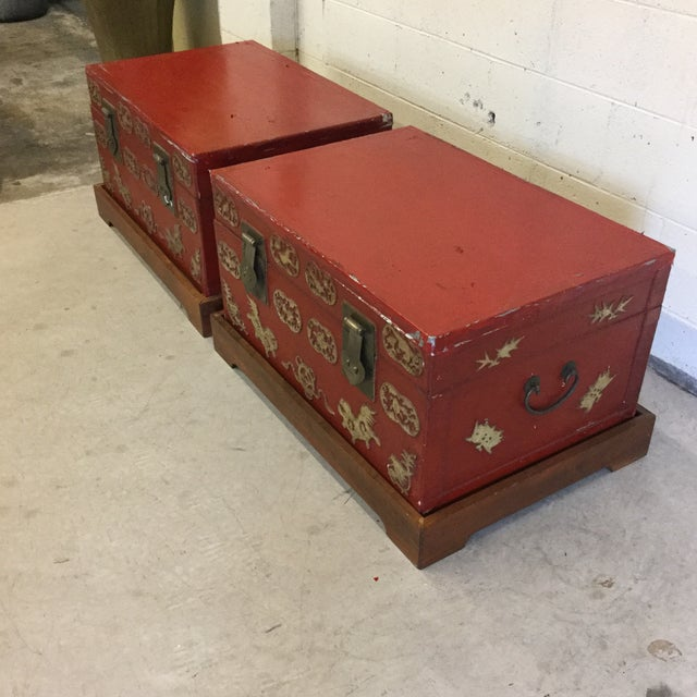 Chinese red and gold leaf accent painted storage trunks that are clearly very vintage. The red paint is peeling in some...