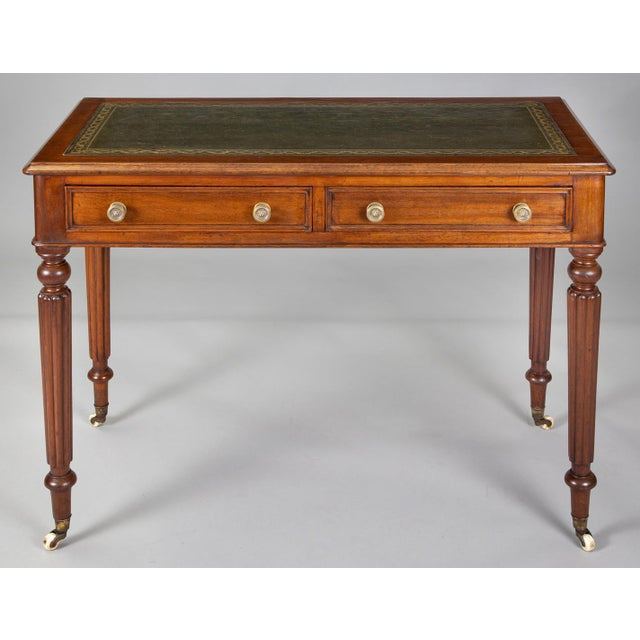 Small late Regency mahogany writing table with green gilt tooled writing surface above two frieze drawers with brass knobs...