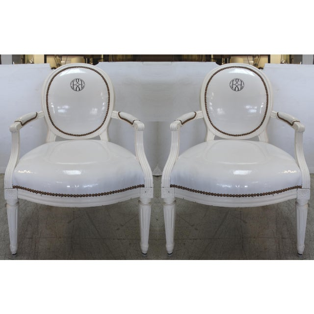 A pair of antique Louis XVI style carved wood fauteuil chairs upholstered in white patent vinyl. The back cushions have...