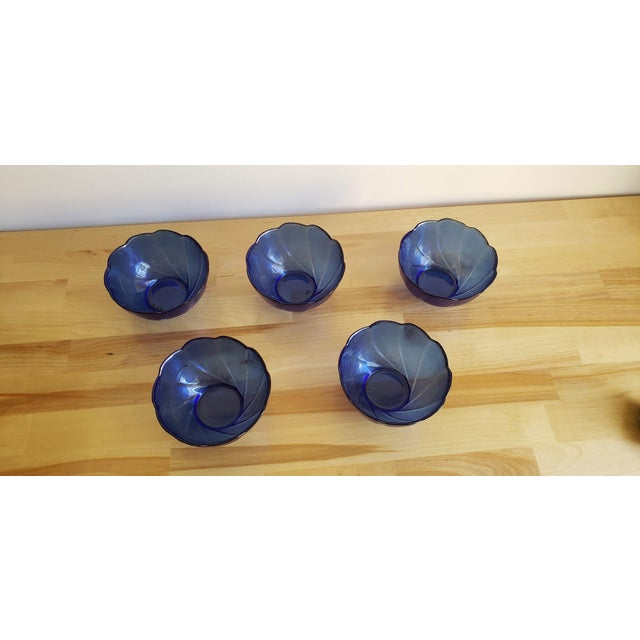 This is an adorable set of five glass bowls in cobalt blue with a swirling shape and scalloped rim.