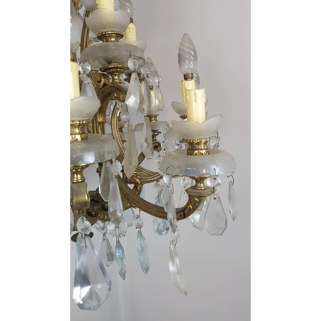 20th century beautiful and elegant chandelier 18 lights golden bronze and crystals circa 1920s. The bronze is richly...