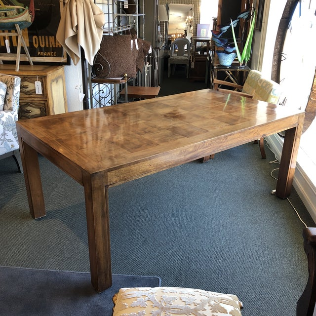 Design Plus Gallery presents a custom dining table. A mottled woodgrain is the star here, pieced in squares and framed in...