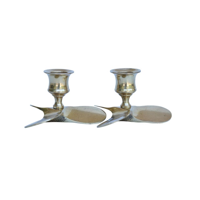 A pair of brass propeller candle holders. Three broad angled blades form the base beneath the simply turned capital....