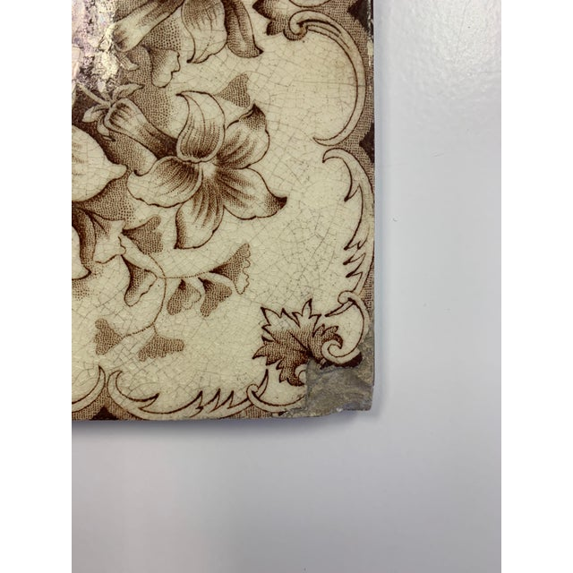 Brown transferware crackle glaze tile with a floral motif and leaf edge design. Edge and corner chips consistent with age.