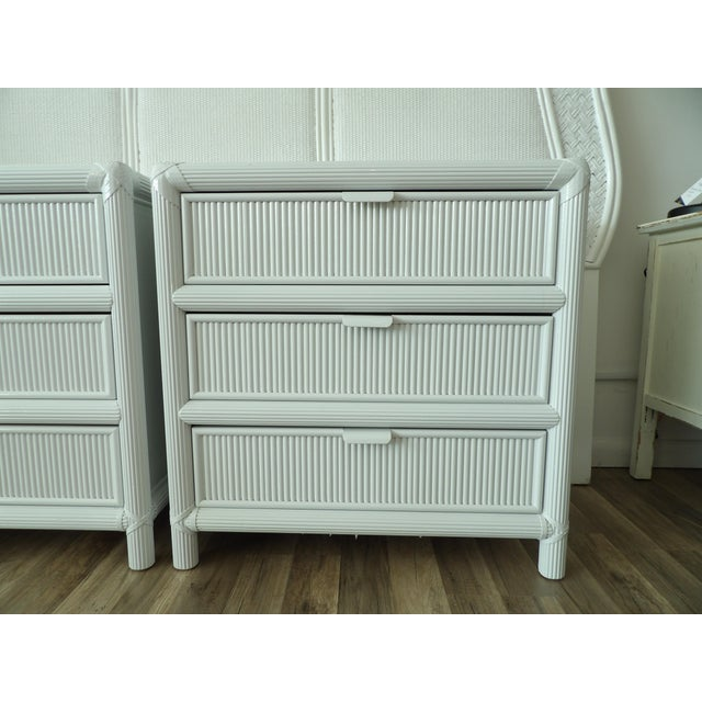 In a crisp white new lacquer finish are this pair of large rattan nightstands. The pair have three smooth sliding drawers...