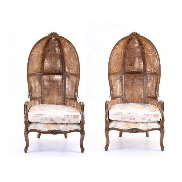 A pair of cane back porter chair featuring wood construction with a muted gold tone finish. These high backed chairs...