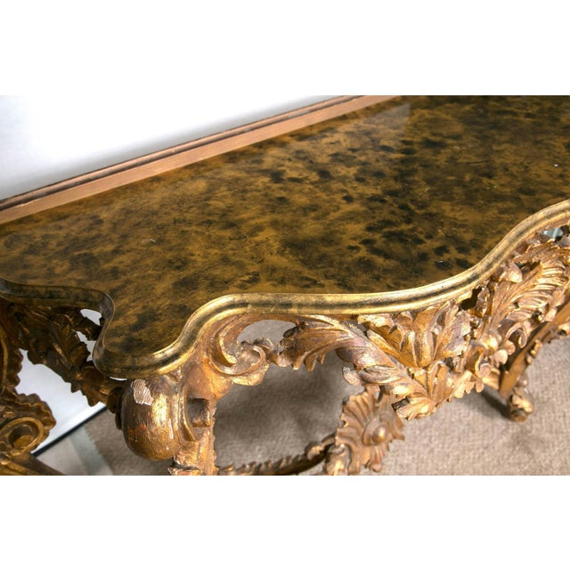 Pair of giltwood consoles with faux marble tops. This pair of giltwood console with faux marble top is a fine...