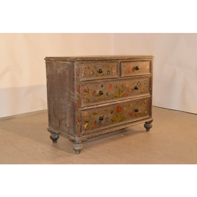 19th century painted pine chest from England with later hand painted floral decoration. The top has a molded edge,...