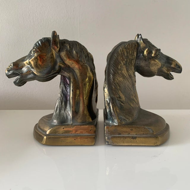 Metal cast horse bookends. Brass patina over original metal. Green felt on the bottom. Horses are neighing in opposite...