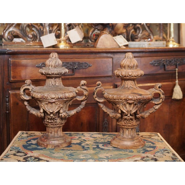 A pair of carved Italian Louis XVI style urns with flame top. The exquisite carving demonstrates the mastery of the...