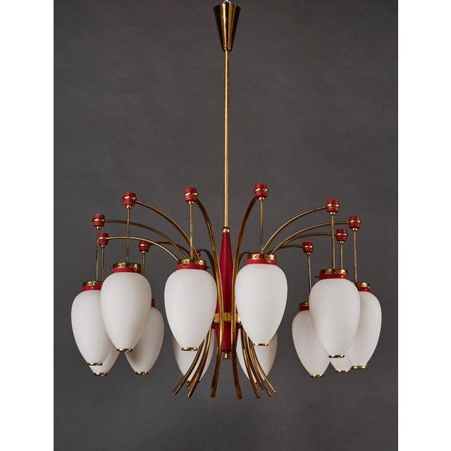 An impresive Italian Stilnovo twelve-globe chandelier in opaline glass, enameled metal and brass.