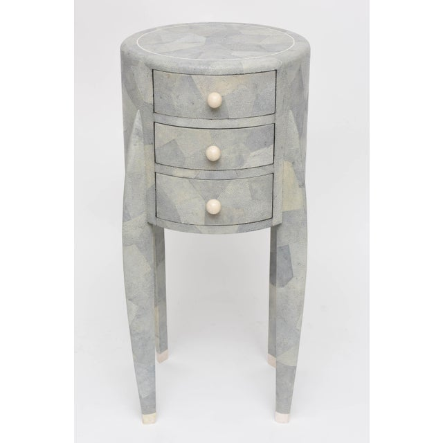 Shades of pale grey, and green all come through in this diminutive patchwork shagreen chest of drawers with creamy bone...