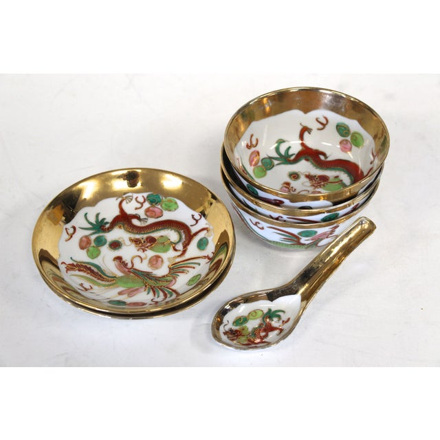 A lovely, hand-painted Chinese soup bowl set that features a dragon and phoenix motif. It has three soup bowls, two...
