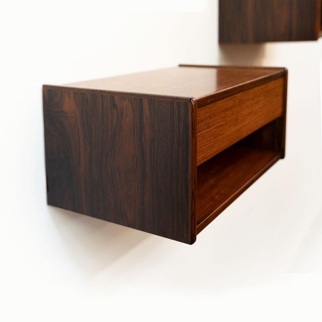 Beautifully designed vintage Danish mid-century floating rosewood nightstands, with single pull-out drawer and open shelf....