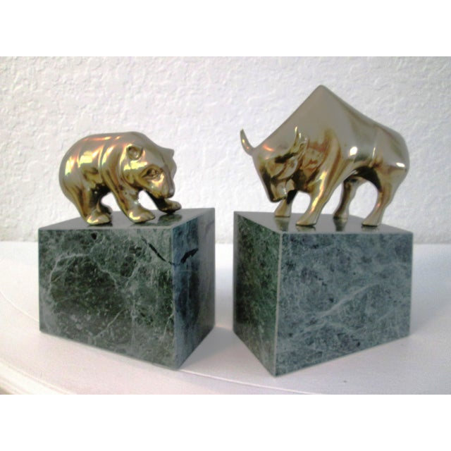 Vintage pair of figural solid brass Wall Street bull and bear bookends mounted on verdigris-green shaded marble bases....