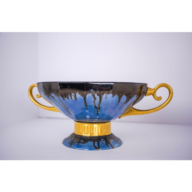 Round footed bowl with a pair of gilded handles and foot collar. The unusual glaze comprises dark blue dripped over...