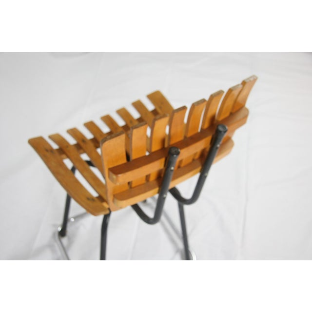 This Mid Century slatted swivel chair is in the style of Arthur Umanoff. The slatted wood chair sits on a black metal...