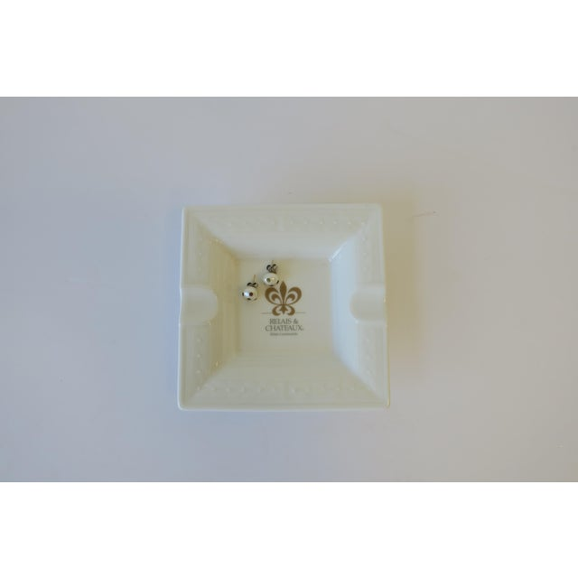 A small square white and gold porcelain dish or ashtray from French luxury hotel brand Chateau & Relias with a beautiful...