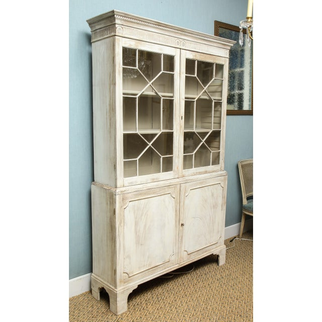 This painted English cabinet has a quiet elegance about it. The piece features two glazed mullioned doors opening to an...